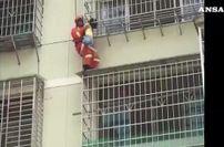 Incastrata tra le inferriate e appesa dal quinto piano, salva